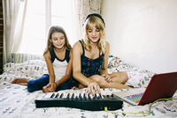 Sisters playing keyboard on bed