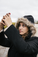 Caucasian woman taking selfie outdoors
