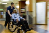 Nurse wheeling patient in hospital waiting area 11018068631| 写真素材・ストックフォト・画像・イラスト素材|アマナイメージズ