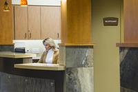 Caucasian receptionist working in office 11018068632| 写真素材・ストックフォト・画像・イラスト素材|アマナイメージズ