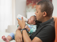 Father feeding baby son