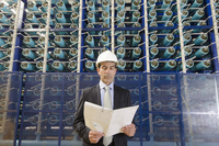 Hispanic businessman reading folder in power plant