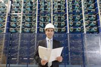 Hispanic businessman smiling in power plant