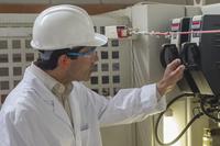 Hispanic technician checking machinery in factory