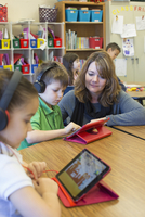 Teacher helping students use digital tablets
