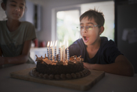 Mixed race boy blowing birthday candles