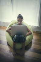 Mixed race girl using laptop in beanbag chair