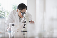 Mixed race scientist using microscope in laboratory 11018069246| 写真素材・ストックフォト・画像・イラスト素材|アマナイメージズ