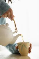 Hispanic woman pouring cup of tea 11018069247| 写真素材・ストックフォト・画像・イラスト素材|アマナイメージズ