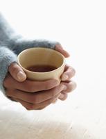 Hispanic woman holding cup of tea 11018069248| 写真素材・ストックフォト・画像・イラスト素材|アマナイメージズ
