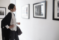 Hispanic woman admiring art in gallery