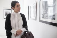 Hispanic woman admiring art in gallery