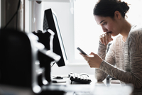 Hispanic woman using cell phone at computer