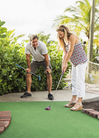 Caucasian couple playing miniature golf