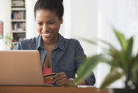 Mixed race woman shopping on laptop
