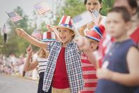 People waving flags at 4th of July parade