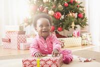 Black baby girl opening Christmas gift