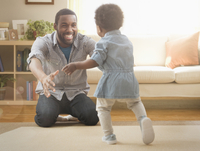 Father and daughter playing in living room