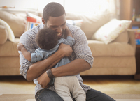Father hugging baby daughter in living room