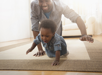 Father and baby daughter crawling on rug
