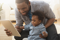 Father and baby daughter using digital tablet