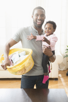 Father holding baby daughter and laundry basket