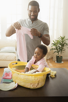 Father and baby daughter folding laundry