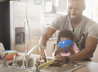 Father holding baby daughter and washing dishes