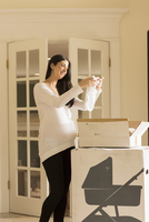 Pregnant Caucasian woman admiring baby clothing