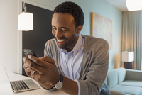Black man using cell phone in living room