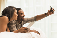 Couple taking selfie on bed