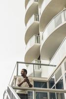 Black man using cell phone on balcony