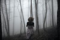 Caucasian woman running in forest 11018069493| 写真素材・ストックフォト・画像・イラスト素材|アマナイメージズ