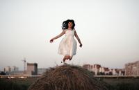 Caucasian woman jumping on haystack 11018069510| 写真素材・ストックフォト・画像・イラスト素材|アマナイメージズ