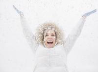 Caucasian woman playing in snow 11018069529| 写真素材・ストックフォト・画像・イラスト素材|アマナイメージズ