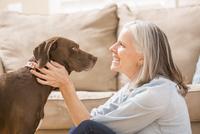 Caucasian woman hugging dog in living room 11018069543| 写真素材・ストックフォト・画像・イラスト素材|アマナイメージズ