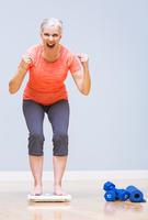 Caucasian woman cheering on scale 11018069549| 写真素材・ストックフォト・画像・イラスト素材|アマナイメージズ