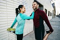 Athletic couple stretching on sidewalk