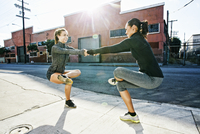 Athletes balancing on sidewalk