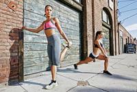 Athletes stretching on sidewalk