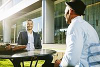 Businessmen talking at table outdoors 11018069703| 写真素材・ストックフォト・画像・イラスト素材|アマナイメージズ