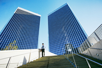 Black businessman standing under highrise buildings