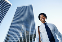 Black businessman smiling under highrise buildings
