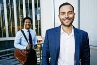 Businessmen smiling outside office building