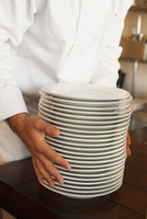 Chef holding stack of plates in restaurant