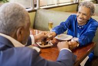 Older couple holding hands in restaurant