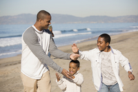 Father and sons high-fiving on beach