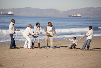 Multi-generation family playing tug-of-war on beach