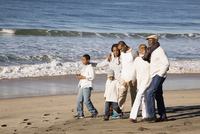 Multi-generation family walking on beach
