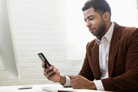 African American businessman using cell phone in office